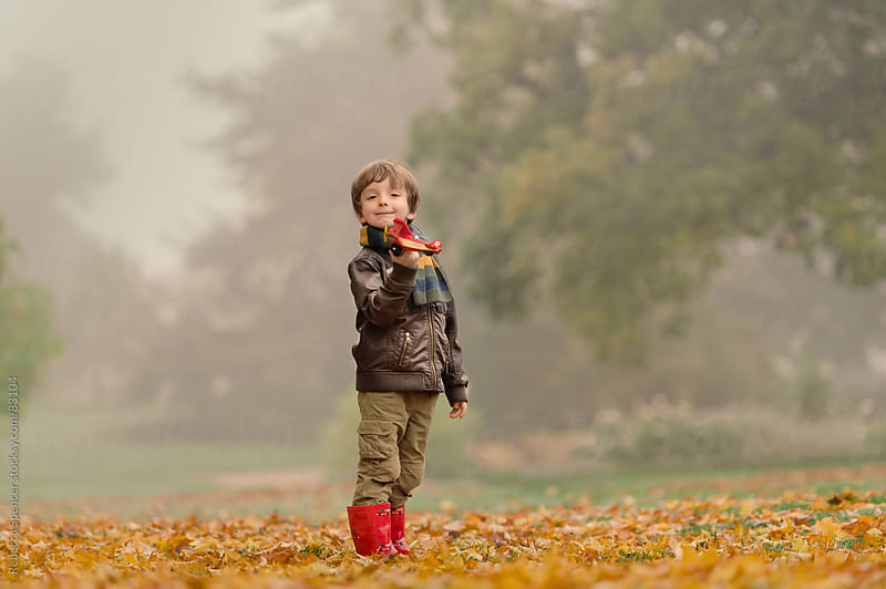 Boy playing with toy in Fall / Autumn leaf scene by Rebecca Spencer for Stocksy United