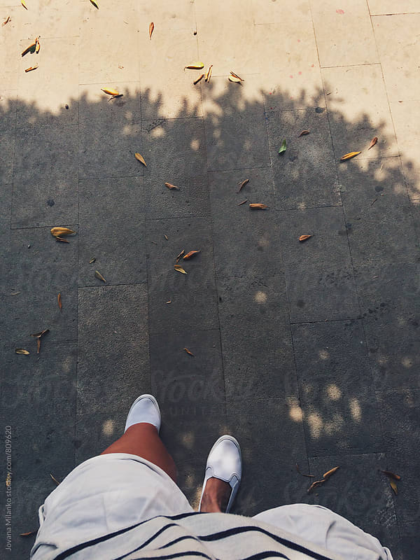 Pov of a woman wearing white in late summer walking down the street  by Jovana Milanko for Stocksy United