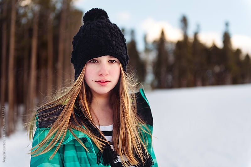 Teenage girl with a direct gaze, outside on a winter's afternoon by Angela Lumsden for Stocksy United