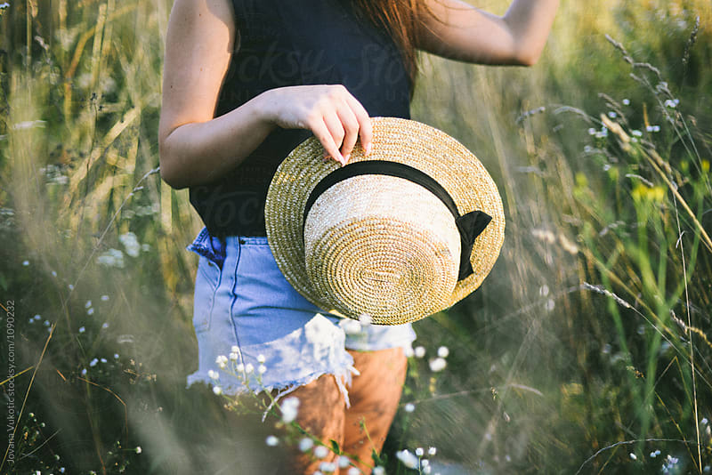 woman holds a straw hat by Jovana Vukotic for Stocksy United