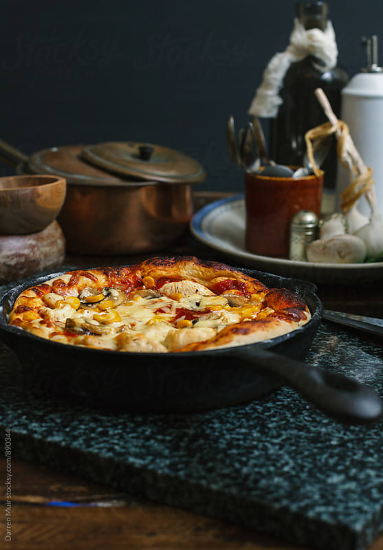 Side view of a freshly baked deep pan skillet pizza. by Darren Muir for Stocksy United