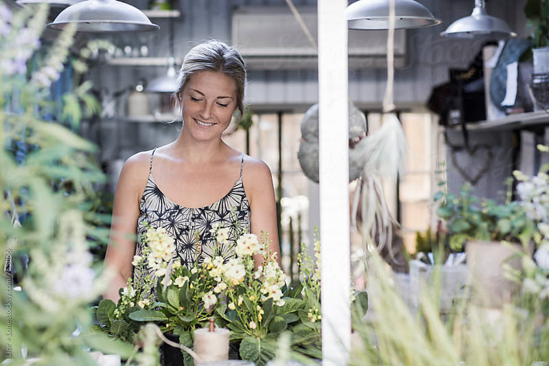Young attractive woman smiling in a flower shop by Lior + Lone for Stocksy United