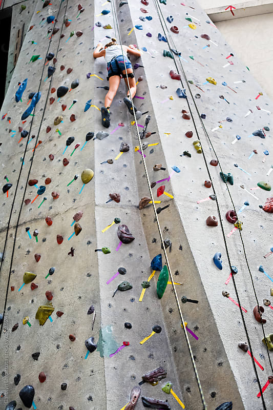 Almost to the top of the rock wall by Carolyn Lagattuta for Stocksy United