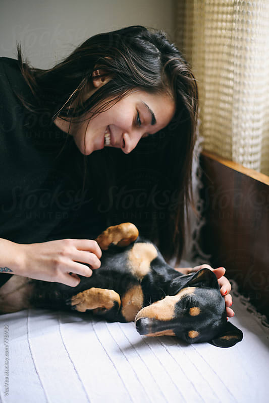 Beautiful woman having a great time with her small black dog  by Marija Mandic for Stocksy United