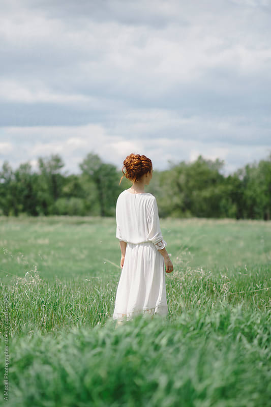 Beautiful young redhead  woman standing in a field in a white dress by Ania Boniecka for Stocksy United