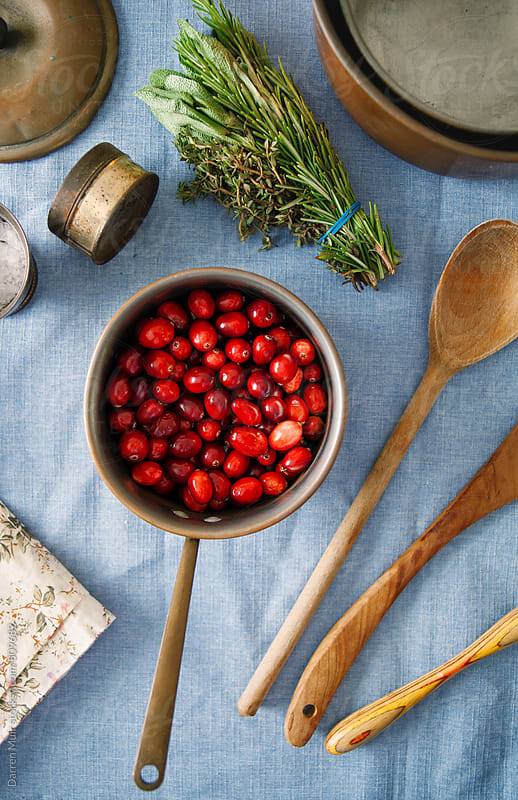 Fresh cranberries in a pot on a kitchen table. by Darren Muir for Stocksy United