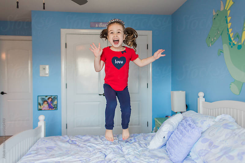 Cute young girl jumping on her bed by Jakob for Stocksy United