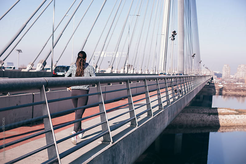 Woman Running on the Bridge by Lumina for Stocksy United