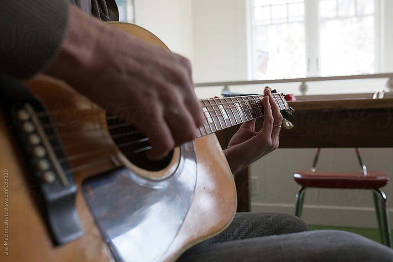 mans hands strumming guitar by Lisa MacIntosh for Stocksy United