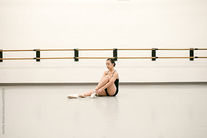 Woman sitting and putting on ballet shoes by Jen Brister for Stocksy United