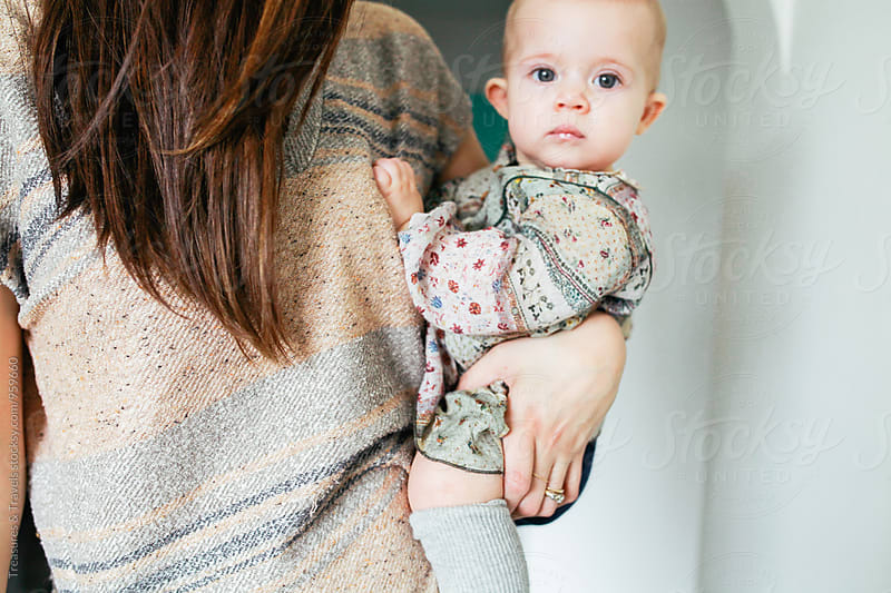 woman holding baby girl on her hip by Treasures & Travels for Stocksy United