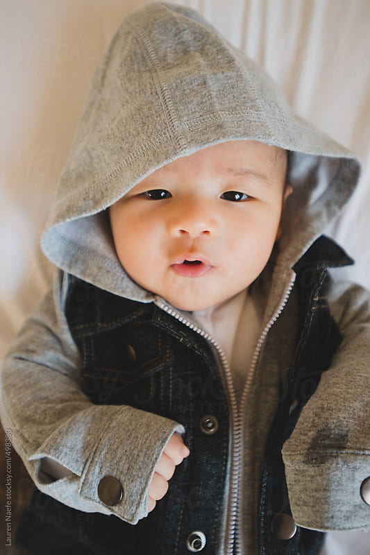 Little baby wearing a hoodie jean jacket by Lauren Naefe for Stocksy United