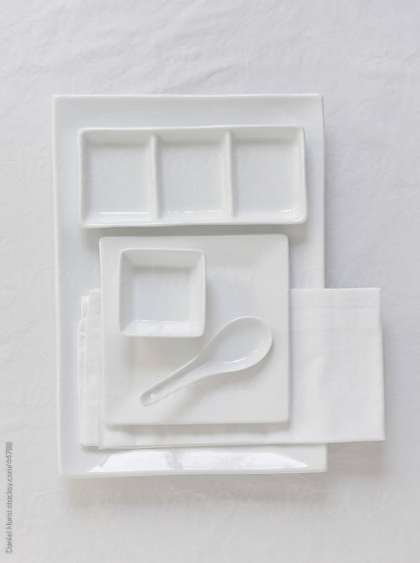White dishes and napkin by Daniel Hurst for Stocksy United