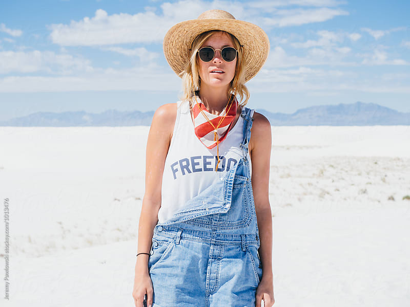 Woman in overalls and straw hat with American bandana by Jeremy Pawlowski for Stocksy United
