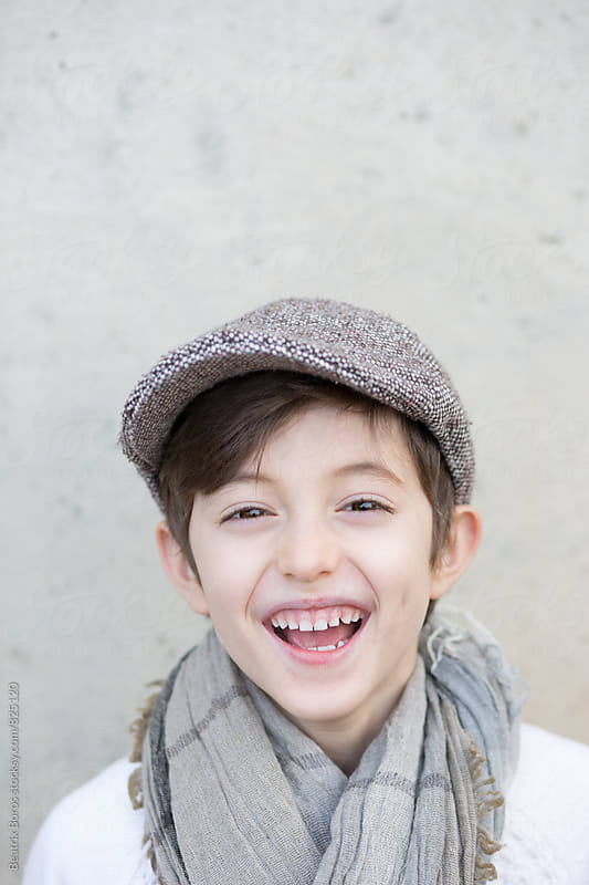 7 years old boy looking at camera laughing by Beatrix Boros for Stocksy United