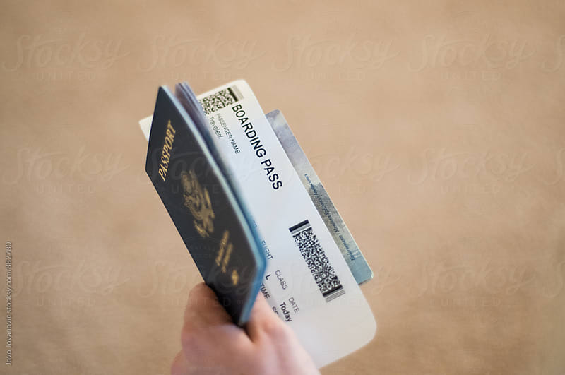 Closeup of a hand holding a passport with a boarding pass in it  by Jovo Jovanovic for Stocksy United