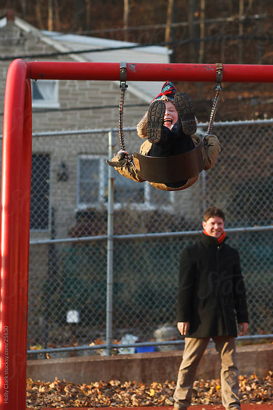Father Pushing Son on City Swingset by Holly Clark for Stocksy United