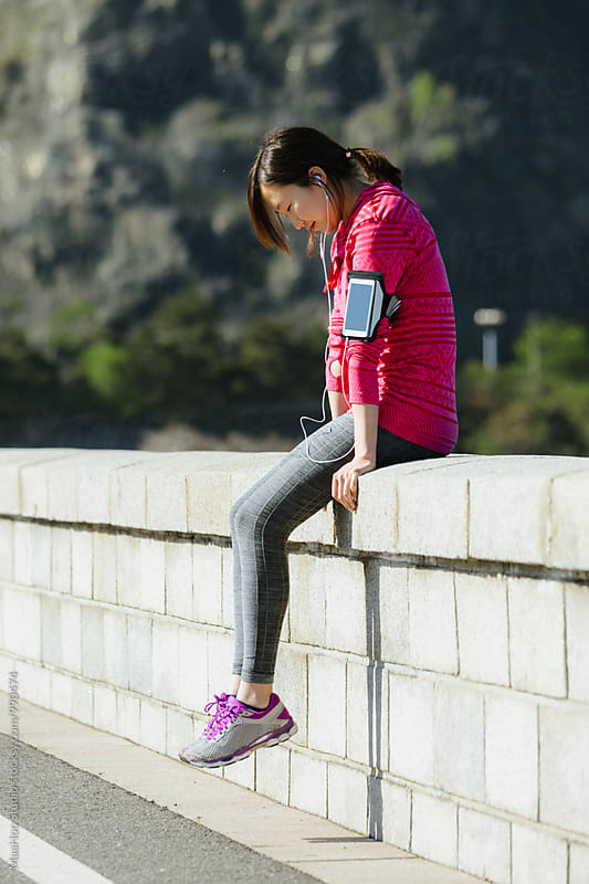 Young woman taking a rest during jogging by MaaHoo Studio for Stocksy United