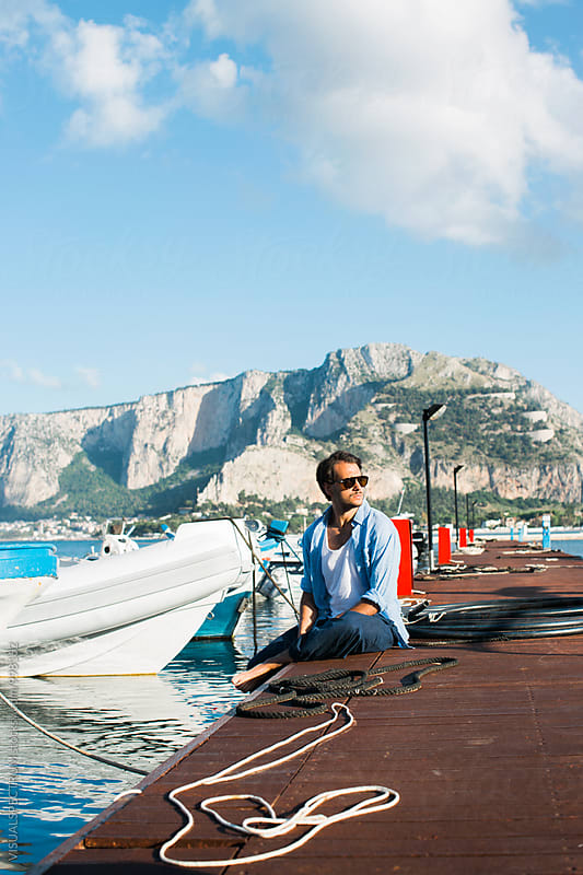 Outdoor Portrait of Handsome Italian Man with Moustache and Sunglasses Sitting on Port Pier by Julien L. Balmer for Stocksy United