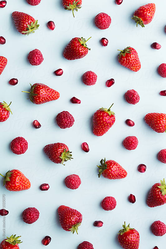 Strawberries, raspberries and pomegranate seeds by Ruth Black for Stocksy United