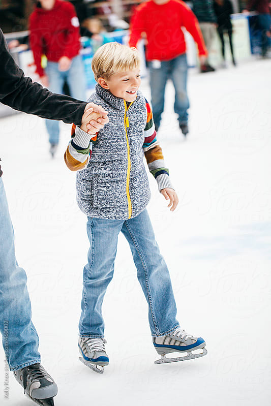 happy boy ice skates with his father by Kelly Knox for Stocksy United