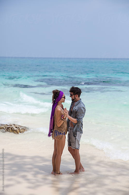Couple having an romantic moment at the beach by Jovo Jovanovic for Stocksy United
