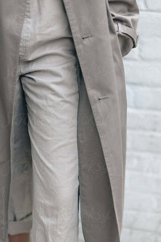 Detail shot of a woman's left leg and coat by Eddie Pearson for Stocksy United