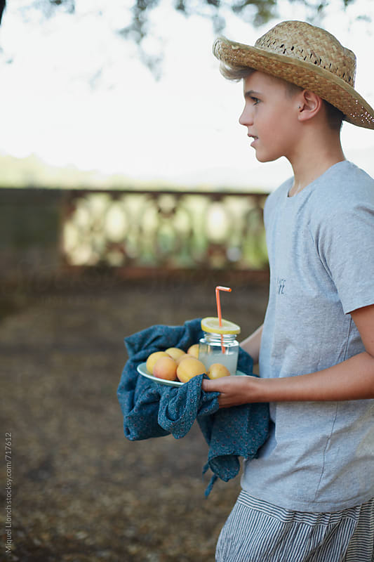 Young man with a plate of fruit and juice by Miquel Llonch for Stocksy United