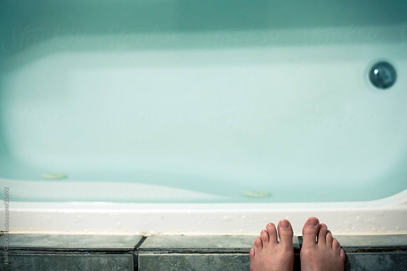 Toes on the edge of a bathtup filled with water by Holly Clark for Stocksy United
