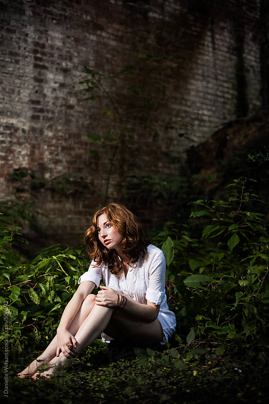 Young redheaded woman sitting in lush greenery by J Danielle Wehunt for Stocksy United