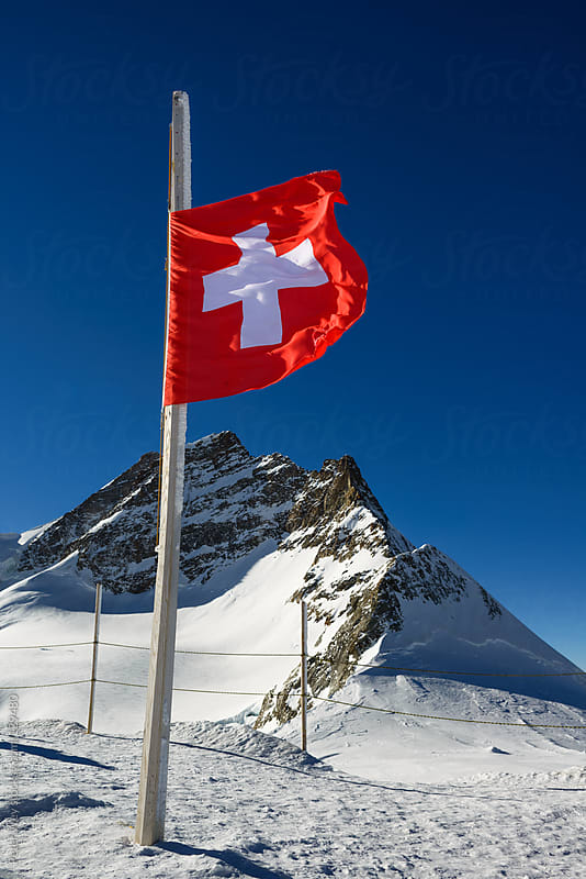 Waving flag of Switzerland with Jungfrau mountain peak by Peter Wey for Stocksy United