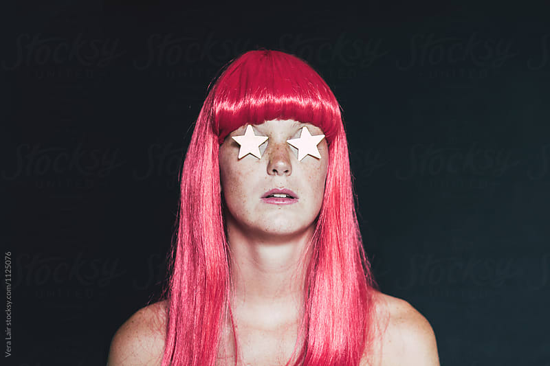 Woman with a wig and eyes hidden by golden stars
