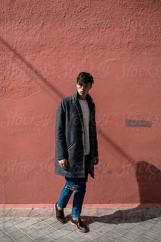 Young Man standing outdoors by Javier Marquez for Stocksy United