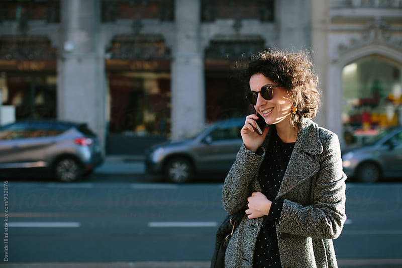 Woman on the phone in the street by Davide Illini for Stocksy United