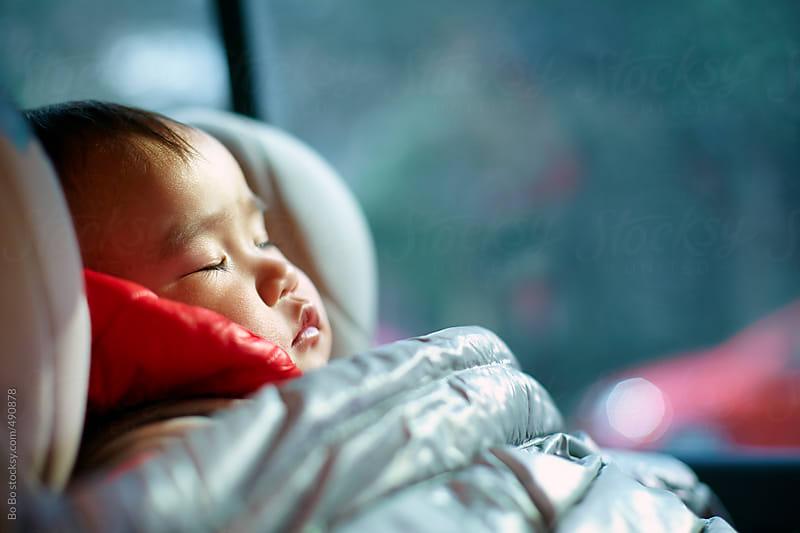 baby girl sleeping in her seat in the car  by Bo Bo for Stocksy United