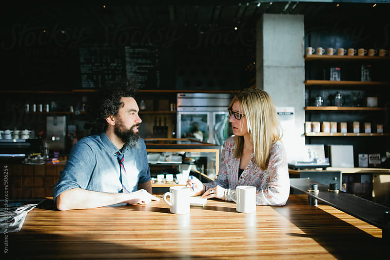 Man and woman having a conversation over coffee in a cafe by Kristine Weilert for Stocksy United