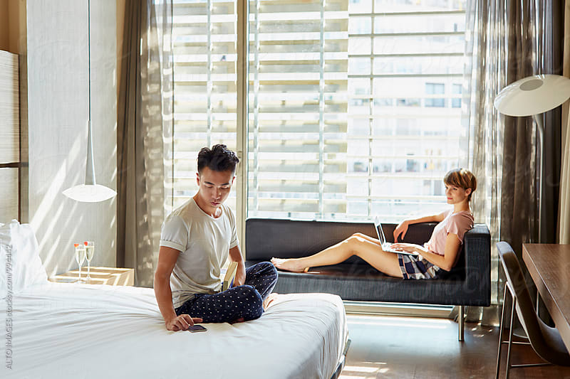 Couple Using Technology In Hotel Room by ALTO IMAGES for Stocksy United
