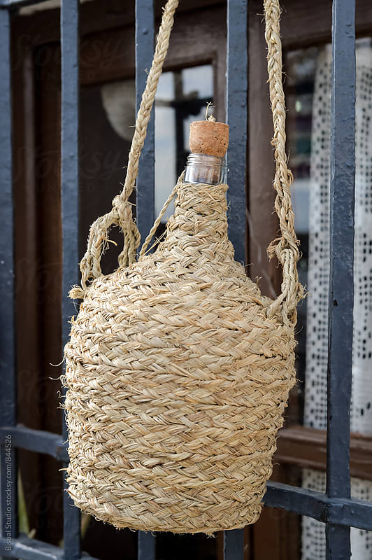 Typical andalusian demijohn with a cover made of straw  by Bisual Studio for Stocksy United