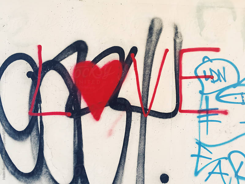 The word Love and a heart painted on a wall. by Helen Rushbrook for Stocksy United