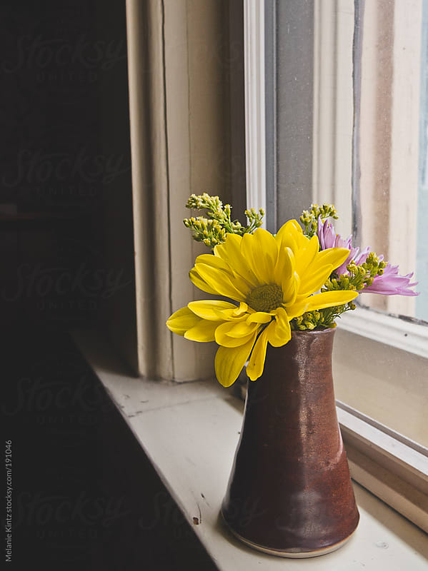 Small flower bouquet on a window sill by Melanie Kintz for Stocksy United
