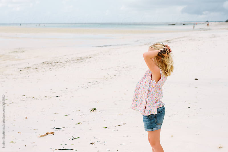 Girl on a beach looking out to sea by Helen Rushbrook for Stocksy United
