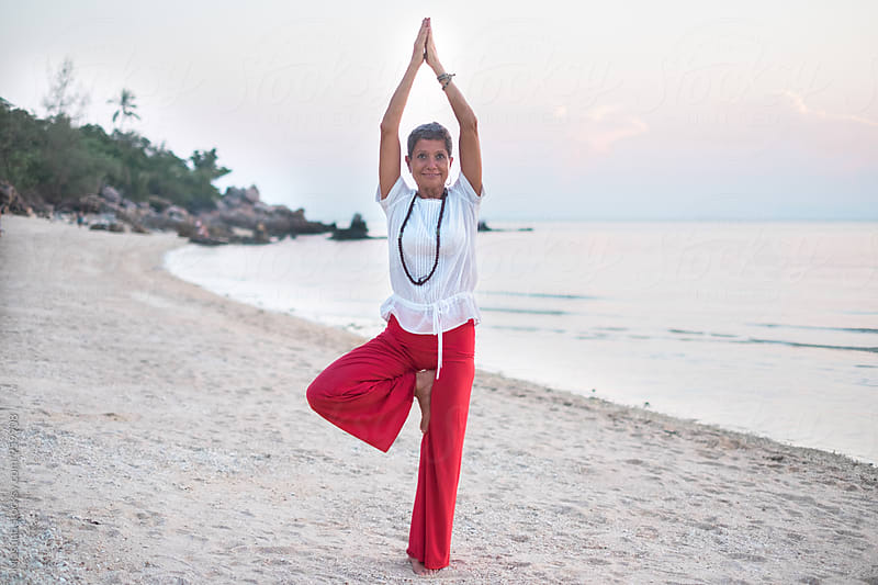 Senior Woman Standing in Yoga Tree Pose at the Beach by Mosuno for Stocksy United