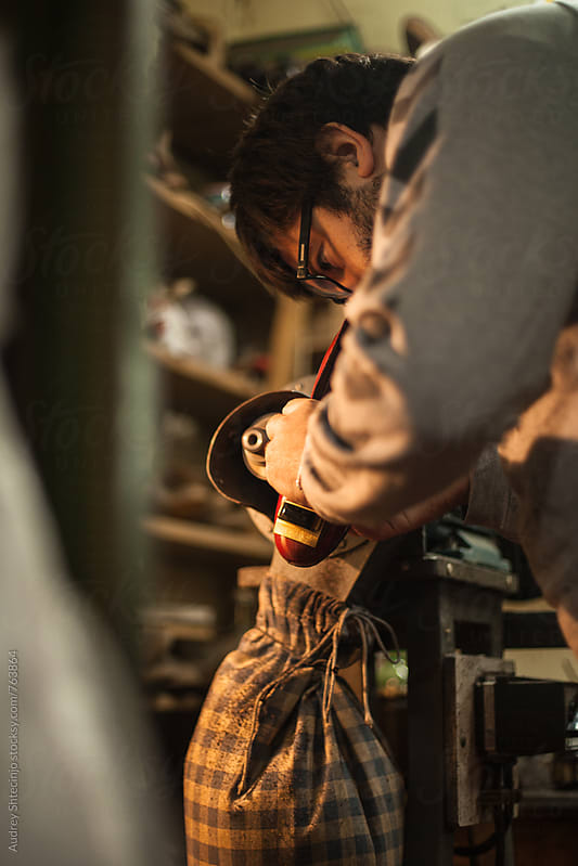 Cobbler repairing old shoes in his workshop by Marko Milanovic for Stocksy United