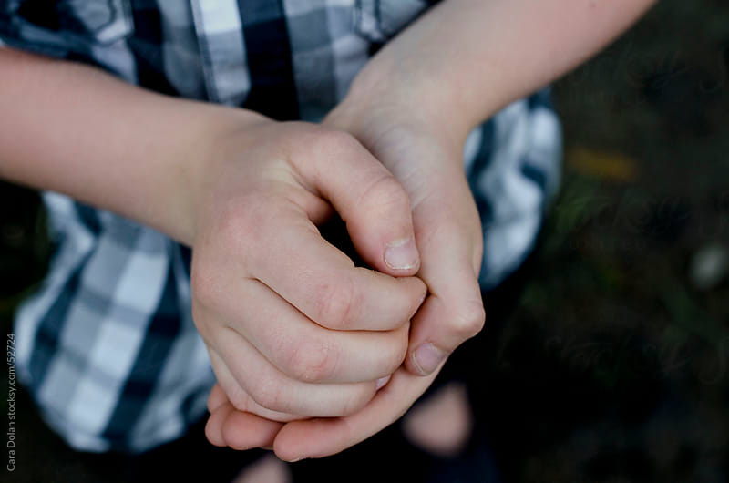 Boy holds something secret in his hands by Cara Slifka for Stocksy United