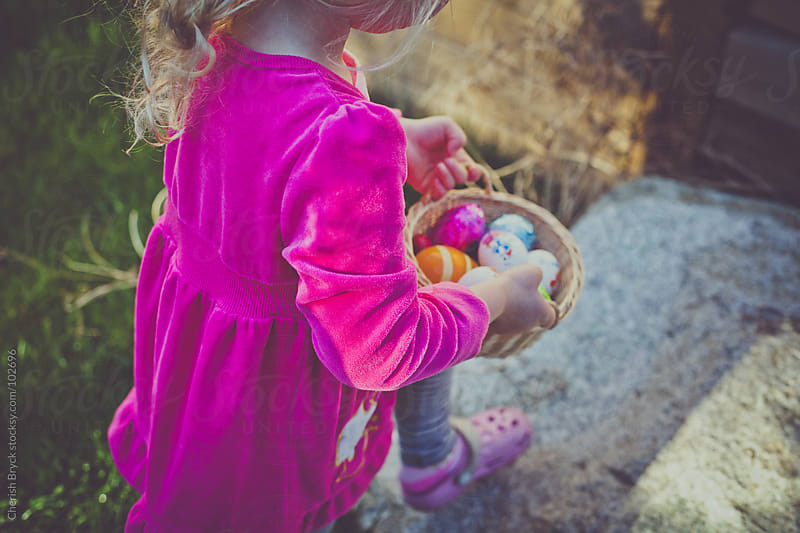 A little girl carries her basket full of chocolate eggs. by Cherish Bryck for Stocksy United