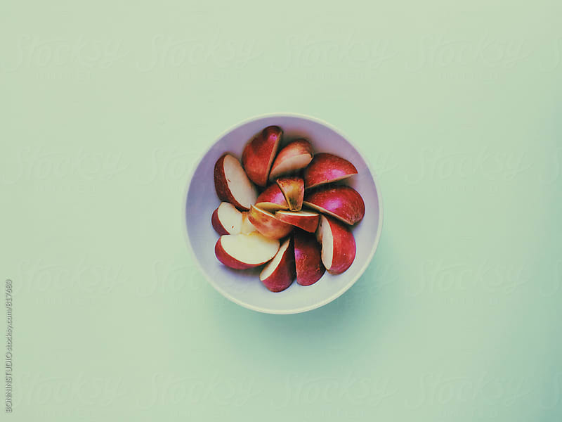 Overhead of a bowl with red apple on green background. by BONNINSTUDIO for Stocksy United