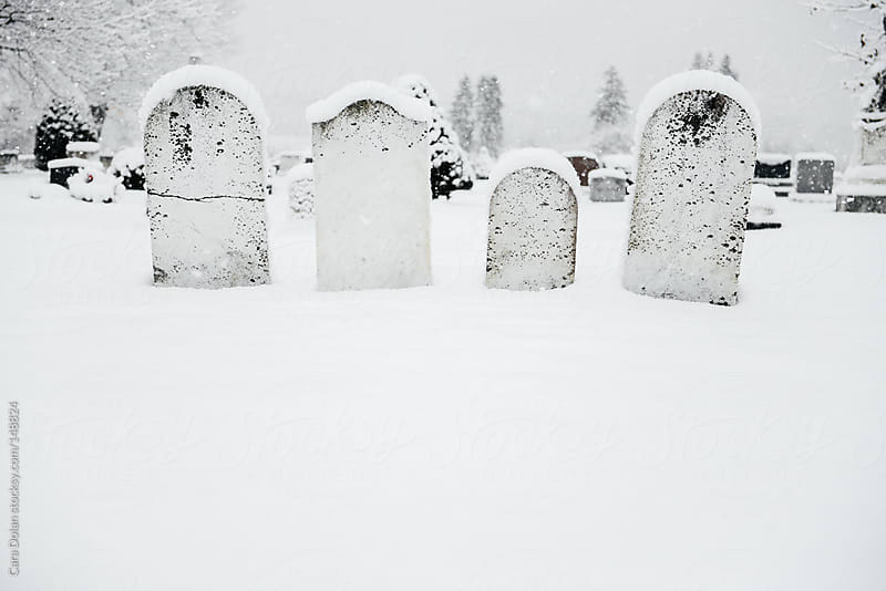 Group of four headstones in a cemetery covered in fresh snow by Cara Dolan for Stocksy United