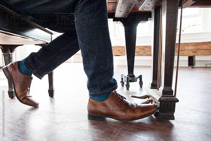 legs underneath piano by Lisa MacIntosh for Stocksy United