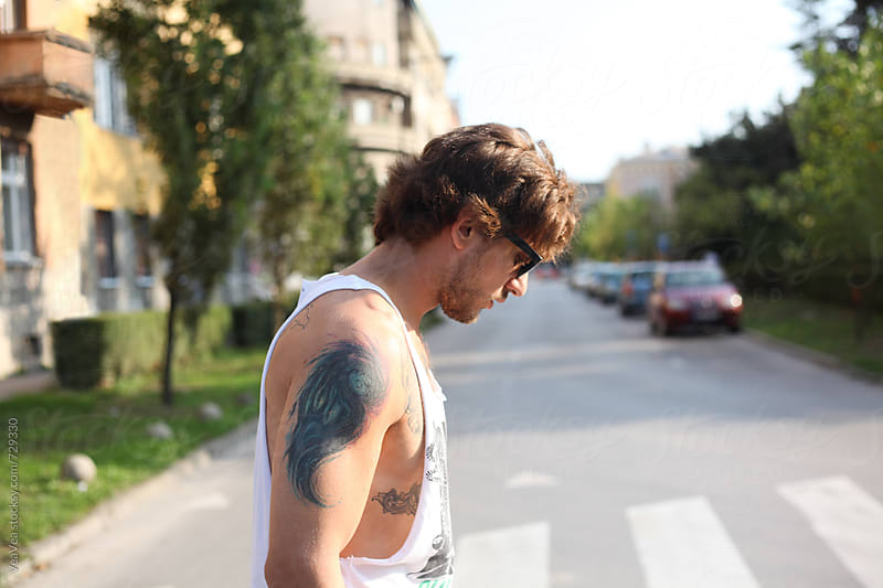 Portrait of a young tattooed man in the street  by Marija Mandic for Stocksy United