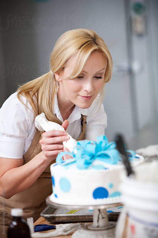 Bakery: Pretty Baker Frosting a Fancy Cake by Sean Locke for Stocksy United